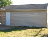 side-of-garage-after-siding-eave-and-steel-door-small